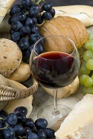 artisan bread, gourmet cheese, two bunches of grapes, and a glass of red wine