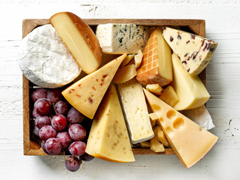assorted cheeses and grapes in a box
