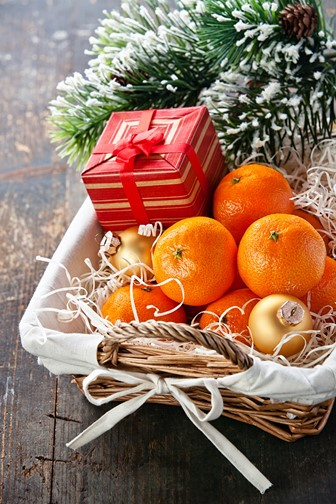 mandarins in a basket with gift box and evergreen branch